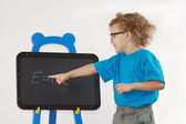 Little cute boy with glasses shows Einstein's formula on blackboard — Foto de Stock