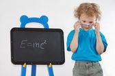 Little amazed boy with glasses shows Einstein's formula on blackboard — Stock Photo
