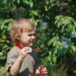 Young boy playing with bubbles on a sunny day — Stock Photo