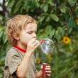 Young blond boy playing with bubbles outdoors — Stok fotoğraf