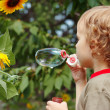 Young blond boy blowing a bubbles outdoors — Stock Photo #11866010