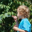 Young blond boy blowing a bubbles outdoors — Stock Photo