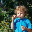 Young boy blowing a bubbles outdoors — Stock Photo #11866367