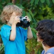 Stock Photo: Young beautiful photographer with a camera shoots her mother