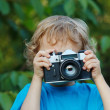 Little cute blond boy with a camera shoots you - Stock Photo