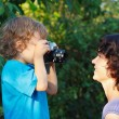 Little cute blond boy with a camera shoots her mother — Stock fotografie