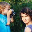 Little blond boy with a camera shoots her mother — Stock Photo #12022587