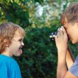Royalty-Free Stock Photo: Young photographer with a camera shoots her brother
