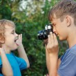 Young photographer with a camera shoots her little brother - Stock Photo
