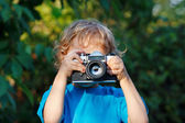 Little blond boy with a camera shoots you — Foto Stock