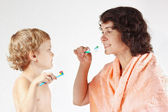 Mother teaches her little son to brush their teeth — Stock Photo