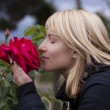 Lady smelling a rose ih a baroque park — Stock Photo
