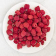 Raspberries on a white plate — Stock Photo