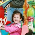 Little girl playing on carousel — Stock Photo