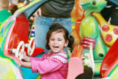 Little girl playing on carousel — Stock Photo