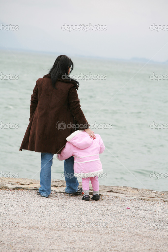 Mother and daughter looking the sea on winter — Stock Photo #11795656