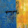 Royalty-Free Stock Photo: Latch the door on the faded blue and yellow wall