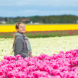 Stock Photo: Girl in colorful tulips field