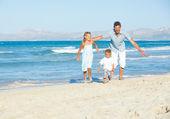Happy family on tropical beach — Stock Photo