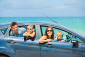 Family of four driving in a car — Stock Photo