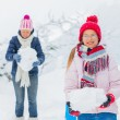 Winter girl throwing snowball with mother — Stock Photo