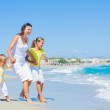 Happy family on tropical beach — Stock Photo #11477676