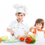 Two smiling kids mixing salad — Stock Photo