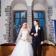 Stock Photo: Groom and bride during wedding ceremony in old town hall interior