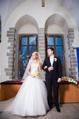 Groom and bride during wedding ceremony in old town hall interior — Stock Photo