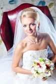 Beautiful bride sitting in red armchair — Stock fotografie