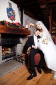 Beautiful groom and bride sitting near fireplace — Stock Photo