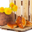 Three pies and dandelions in  clay pot — Stock Photo
