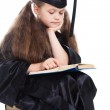 Girl in black academic cap and gown reading big blue book — Stock Photo