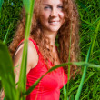 Beautiful girl in red among high green grass of summer meadow — Stock Photo
