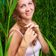 Beautiful girl braiding a plait among high green grass of summer meadow — Stock Photo