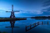 Molino de viento cerca al lago al atardecer — Foto de Stock