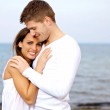 Couple Cuddling at the Beach Looking Happy — Stock Photo #11744261