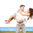 Handsome Man Carrying His Girlfriend in a Windy Beach — Stock Photo