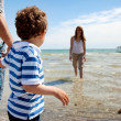 Stock Photo: Little Boy Looking at His Mom Dipping in the Water