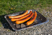 Sausages on one time use grill — Stock Photo