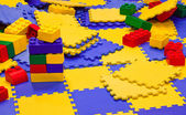 Multicolored plastic toy bricks and carpets — Stock Photo