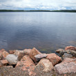 Coast of lake with granite stones - Stockfoto