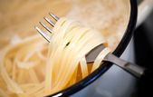 Noodles in the pan with fork — Stock Photo