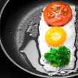 Original breakfast theme. Fried egg with tomato and greens in shape of Traffic Light in a frying pan - Stock Photo