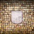 Golden mosaic wall with empty emblem element — Stock Photo