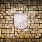 Golden mosaic wall with empty emblem element — Stock Photo