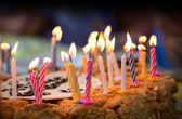 Colorful candles on birthday cake — Stock Photo