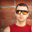 Young man in black sunglasses with reflected fire — Stock Photo