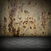 Grunge interior with rusted metal wall and diamond metal plate floor — Stock Photo