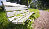 White park bench with grass growing through — Stock Photo